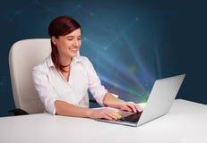 Mujer hermosa que se sienta en el escritorio y que pulsa en la computadora portátil con abstra Fotos de archivo