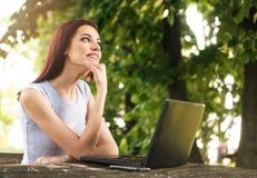 Mujer hermosa que se sienta en el parque, usando un ordenador portátil Fotos de archivo