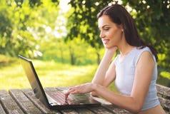 Mujer hermosa que se sienta en el parque, usando un ordenador portátil Fotografía de archivo libre de regalías