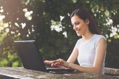 Mujer hermosa que se sienta en el parque, usando un ordenador portátil Foto de archivo