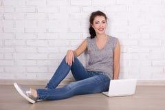 Mujer hermosa que se sienta en el piso con el ordenador portátil sobre bric blanco Fotografía de archivo libre de regalías