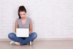 Mujer hermosa que se sienta en el piso con el ordenador portátil y el espacio encima Fotos de archivo