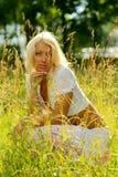 Mujer hermosa que se sienta en hierba en prado Foto de archivo libre de regalías