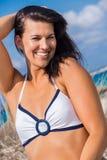 Mujer hermosa que se sienta en la arena de oro de la playa Imagen de archivo libre de regalías