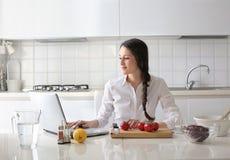 Mujer hermosa que se sienta en la cocina y que intenta cocinar Fotos de archivo libres de regalías
