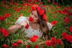 Mujer hermosa que se sienta en la flor de la amapola Imagenes de archivo