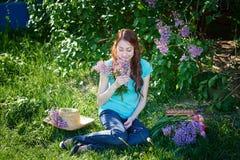 Mujer hermosa que se sienta en la hierba en el parque de la primavera Foto de archivo libre de regalías