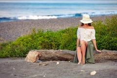 Mujer hermosa que se sienta en la roca imagen de archivo