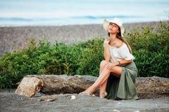 Mujer hermosa que se sienta en la roca imagenes de archivo