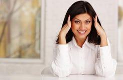 mujer hermosa que se sienta en la tabla y que toca su cabeza Imagen de archivo