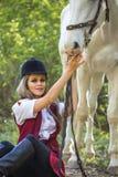 Mujer hermosa que se sienta en la tierra con el caballo marrón cerca de ella Fotos de archivo