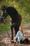 Mujer hermosa que se sienta en la tierra con el caballo marrón cerca de ella Foto de archivo libre de regalías