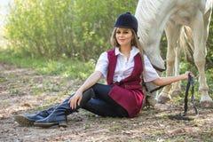 Mujer hermosa que se sienta en la tierra con el caballo marrón cerca de ella Imagenes de archivo