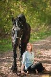 Mujer hermosa que se sienta en la tierra con el caballo marrón cerca de ella Fotos de archivo libres de regalías