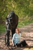 Mujer hermosa que se sienta en la tierra con el caballo marrón cerca de ella Imágenes de archivo libres de regalías