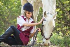 Mujer hermosa que se sienta en la tierra con el caballo marrón cerca de ella Imagen de archivo