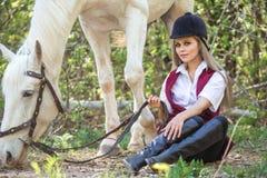Mujer hermosa que se sienta en la tierra con el caballo marrón cerca de ella Imagen de archivo libre de regalías