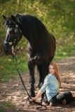 Mujer hermosa que se sienta en la tierra con el caballo marrón cerca de ella Fotografía de archivo libre de regalías