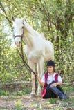 Mujer hermosa que se sienta en la tierra con el caballo marrón cerca de ella Fotografía de archivo