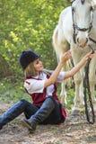 Mujer hermosa que se sienta en la tierra con el caballo marrón cerca de ella Foto de archivo