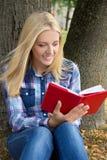 Mujer hermosa que se sienta en libro del parque y de lectura Fotografía de archivo libre de regalías