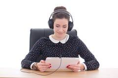 Mujer hermosa que se sienta en oficina y música que escucha en la tableta Fotos de archivo libres de regalías