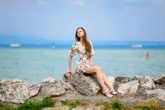 Mujer hermosa que se sienta en roca sobre el mar Fotos de archivo libres de regalías