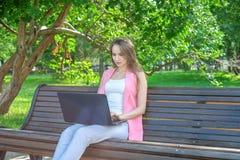 Mujer hermosa que se sienta en un banco de parque usando un ordenador portátil imagen de archivo
