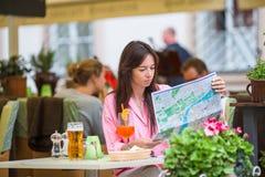 Mujer hermosa que se sienta en un café al aire libre con el mapa El turista feliz disfruta de días de fiesta europeos en el resta Fotos de archivo