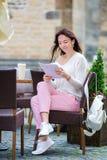 Mujer hermosa que se sienta en un café de consumición al aire libre del café Turista feliz con el periódico en el restaurante al  Fotografía de archivo