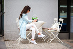 Mujer hermosa que se sienta en un café de consumición al aire libre del café Turista feliz con el teléfono móvil en el restaurant Imagen de archivo libre de regalías