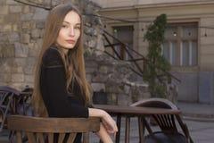 Mujer hermosa que se sienta en un café de la calle Fotografía de archivo libre de regalías