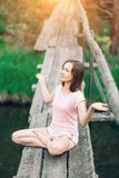 Mujer hermosa que se sienta en un puente de madera y una sonrisa Yoga, naturaleza, salud foto de archivo