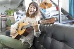Mujer hermosa que se sienta en un sofá y que toca la guitarra Imágenes de archivo libres de regalías