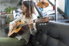 Mujer hermosa que se sienta en un sofá y que toca la guitarra Fotografía de archivo