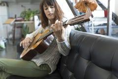 Mujer hermosa que se sienta en un sofá y que toca la guitarra Fotografía de archivo libre de regalías