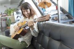 Mujer hermosa que se sienta en un sofá y que toca la guitarra Foto de archivo