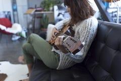 Mujer hermosa que se sienta en un sofá y que toca la guitarra Foto de archivo libre de regalías