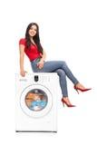 Mujer hermosa que se sienta en una lavadora imagenes de archivo