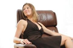 Mujer hermosa que se sienta en una silla fácil Foto de archivo