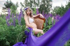 mujer hermosa que se sienta en una silla rodeada por el campo de flores Fotografía de archivo libre de regalías