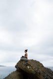 Mujer hermosa que se sienta encima de una roca y de meditar Fotos de archivo libres de regalías