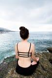 Mujer hermosa que se sienta encima de una roca y de meditar Imagen de archivo libre de regalías