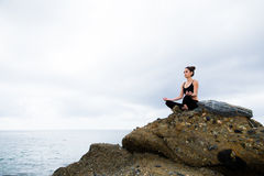 Mujer hermosa que se sienta encima de una roca y de meditar Foto de archivo