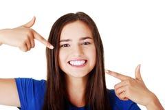 Mujer hermosa que señala en sus dientes blancos perfectos. Imagen de archivo