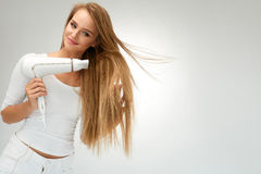 Mujer hermosa que seca el pelo recto usando el secador peluquería imagen de archivo libre de regalías