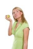 Mujer hermosa que soña y que sostiene una manzana verde Imagen de archivo libre de regalías