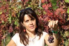Mujer hermosa que sonríe con un pequeño manojo de uvas en otoño Imagen de archivo libre de regalías