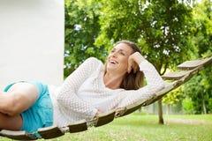 Mujer hermosa que sonríe en la hamaca al aire libre Imágenes de archivo libres de regalías