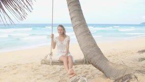 Mujer hermosa que sonríe en un oscilación en la playa metrajes